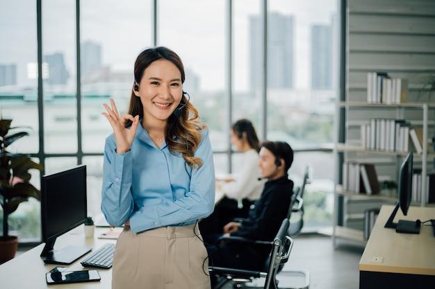 Портрет улыбающейся жизнерадостной службы поддержки с гарнитурой, показывающей нормальный жест.