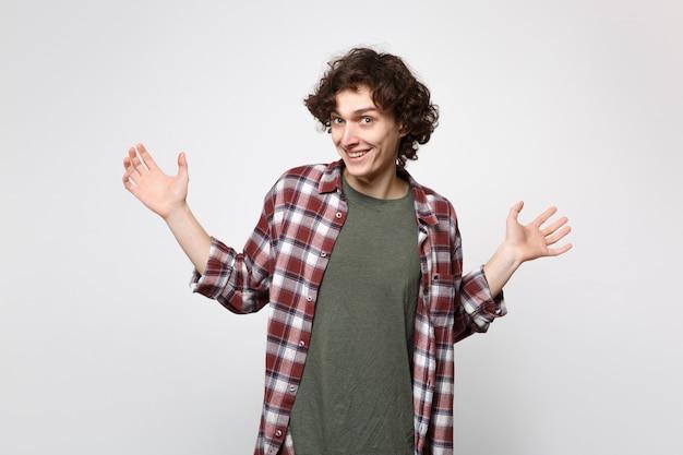スタジオで白い背景に分離された手を立って広げてカジュアルな服を着て笑顔の陽気な興奮した若い男の肖像画。人々の誠実な感情、ライフスタイルのコンセプト。コピースペースをモックアップします。