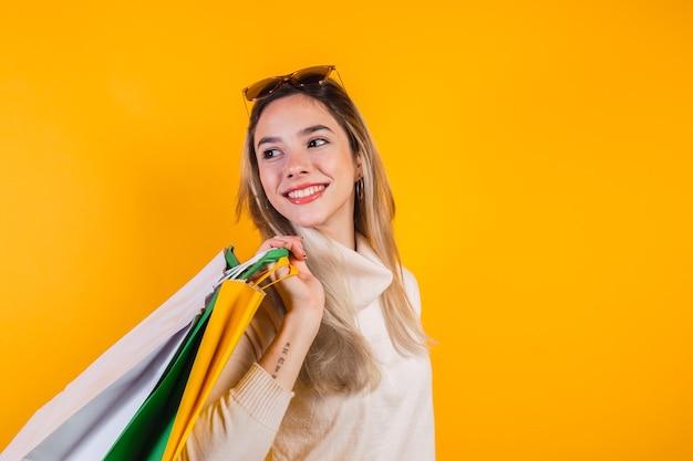 많은 쇼핑백을 들고 웃는 쾌활한 여자의 초상화.