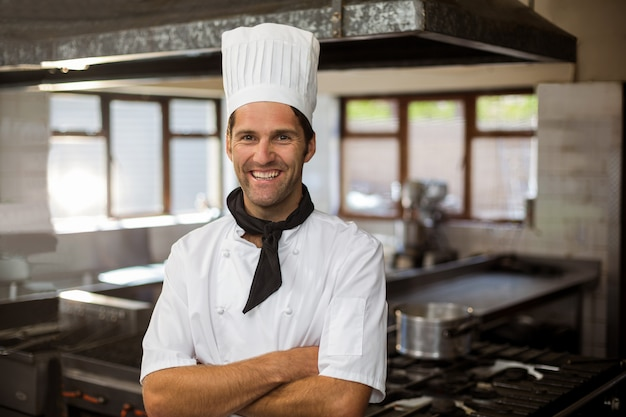 Портрет улыбающегося шеф-повара, стоя со скрещенными руками