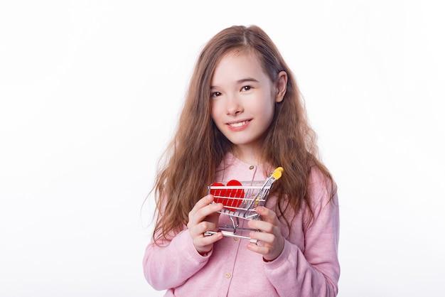ショッピングカートと赤い紙の心を持って笑顔の子供の女の子の肖像画