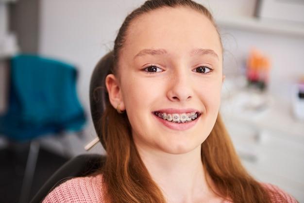 Портрет улыбающегося ребенка с брекетами в кабинете стоматолога