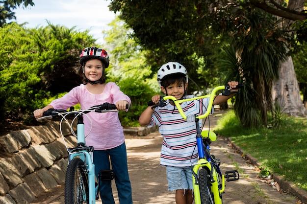 공원에서 자전거와 함께 서 웃는 어린이의 초상