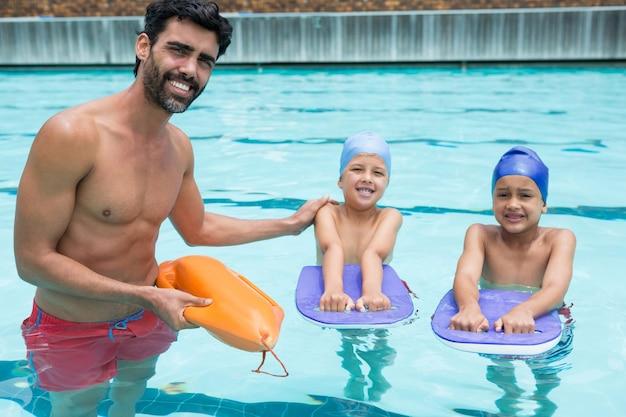 레저 센터에서 수영장에서 수영하는 아이들을 돕는 웃는 코치의 초상화
