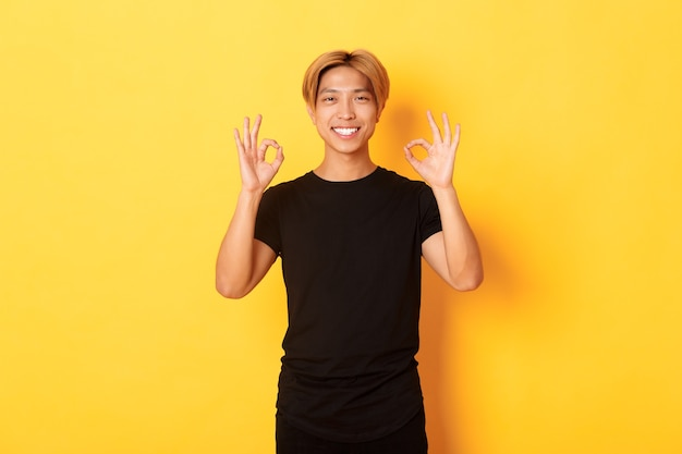 Портрет улыбающегося уверенного в себе азиатского парня, выглядящего довольным, показывая нормальный жест, желтая стена