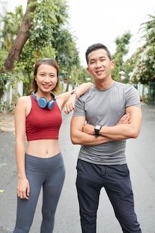 Портрет улыбающейся уверенно подходящей молодой азиатской пары, стоящей на улице и смотрящей в камеру после тренировки