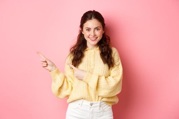 분홍색 벽에 서있는 결정된 얼굴로 홍보 텍스트를 보여주는 로고 왼쪽 손가락을 가리키는 웃는 자신감 여자의 초상화.