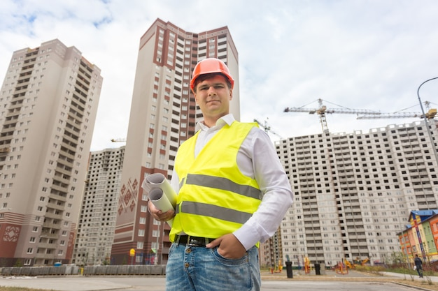 建設現場に立って青写真を持っている笑顔の建設エンジニアの肖像画