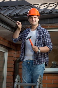 家の屋根の下のステップはしごで笑顔の建設労働者の肖像画