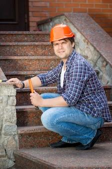 Портрет улыбающегося строителя, ремонтирующего каменную лестницу