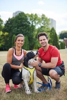 トレーニング後の笑顔のカップルとその犬の肖像画