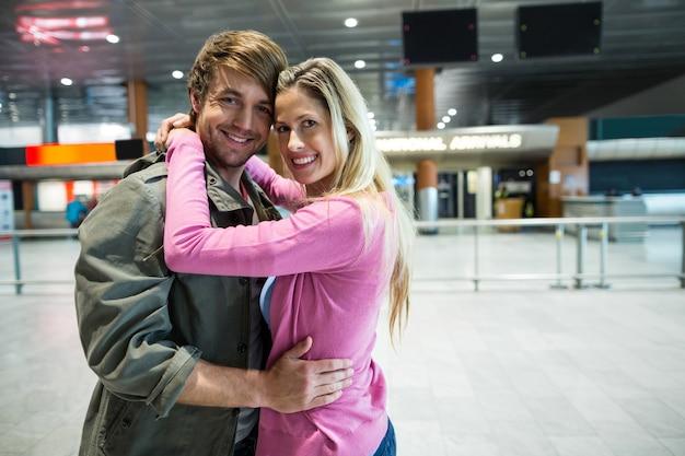 Портрет улыбающейся пары, обнимающей друг друга в зоне ожидания