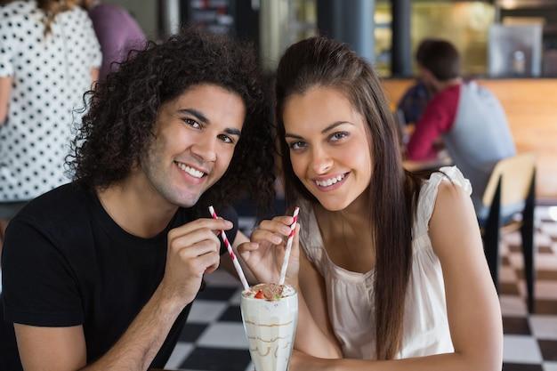 レストランでドリンクを持っている笑顔のカップルの肖像画
