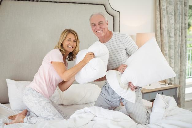 ベッドの上で枕投げを持っているカップルの笑顔の肖像画