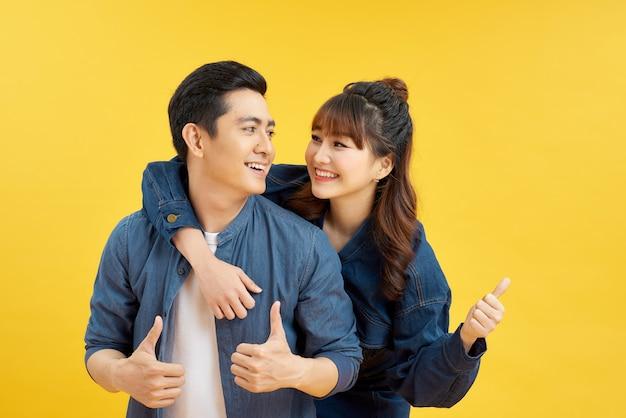 黄色の背景の上に分離されたピギーバックライドをしながら一緒に親指を示す笑顔のカップルの男性と女性の肖像画