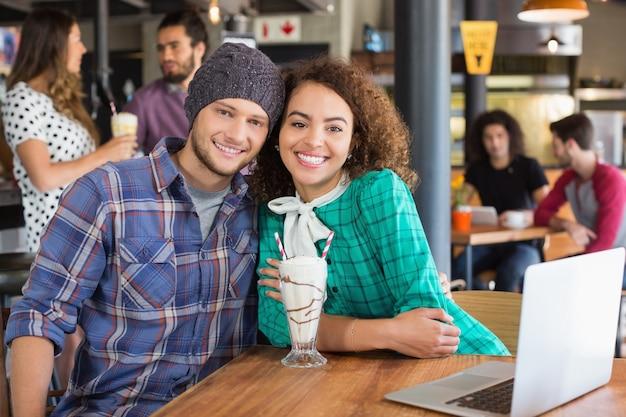 レストランに座っている笑顔のカップルの肖像画