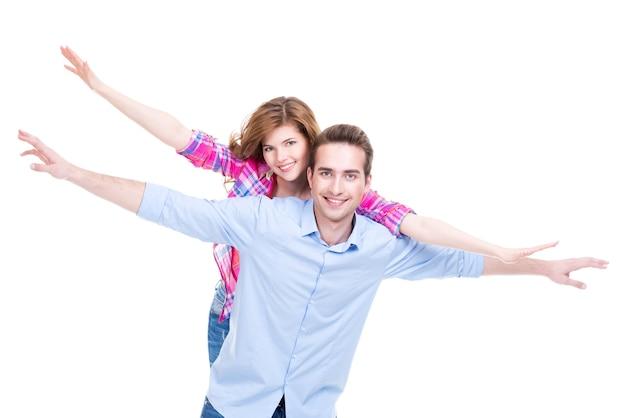 孤立した上げられた手で立っている笑顔のカップルの肖像画
