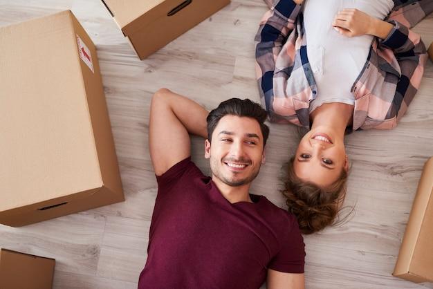 Портрет улыбающейся пары, отдыхающей от переезда домой