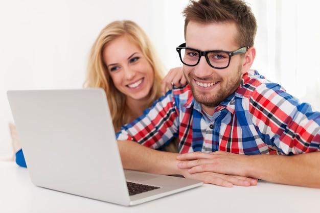 Портрет улыбающейся пары с ноутбуком