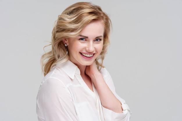 スタジオで白いシャツを着て笑顔の巻き毛の女性の肖像画