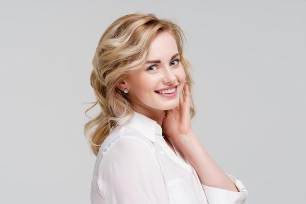 灰色の背景に分離された白いシャツの笑顔の巻き毛の女性の肖像画