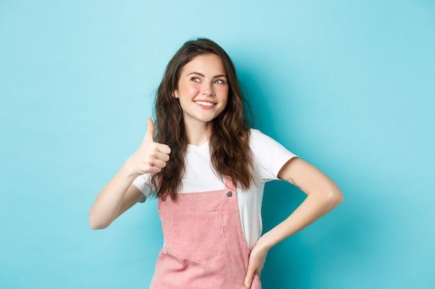 巻き毛の髪型で笑顔のかわいい女の子の肖像画、親指を上に表示し、左上隅のバナーを思慮深く見て、店の販売を賞賛し、青い背景に立っています。