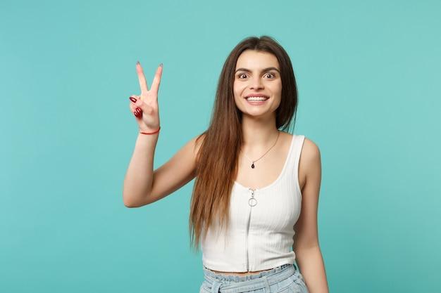 스튜디오의 파란색 청록색 벽 배경에 격리된 승리 기호를 보여주는 가벼운 캐주얼 옷을 입고 웃고 있는 귀여운 젊은 여성의 초상화. 사람들은 진심 어린 감정, 라이프 스타일 개념입니다. 복사 공간을 비웃습니다.