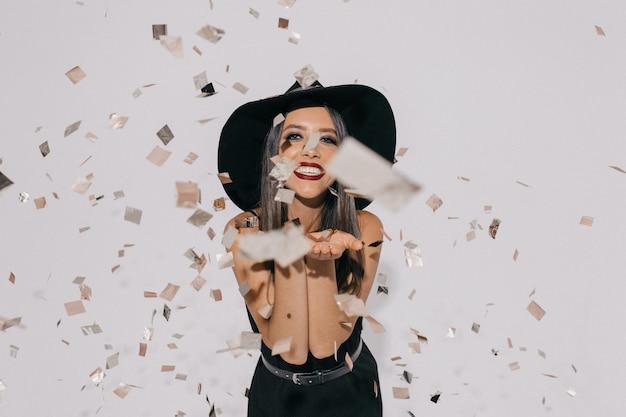 トレンディな黒のドレスと帽子で踊っている女の子の笑顔の肖像画。長い髪の若い女性モデルが紙吹雪の部屋で浮気します。
