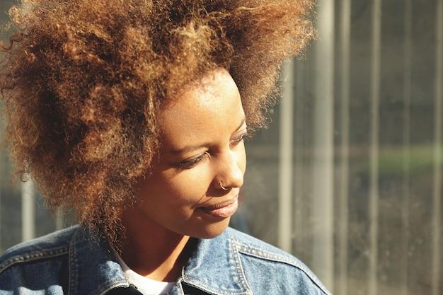 デニムジャケットを着ている彼女の鼻にリングを持つ笑顔の浅黒い女性の肖像画