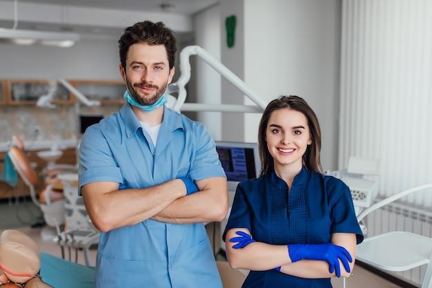 彼女の同僚と腕を組んで立っている笑顔の歯科医の肖像画。