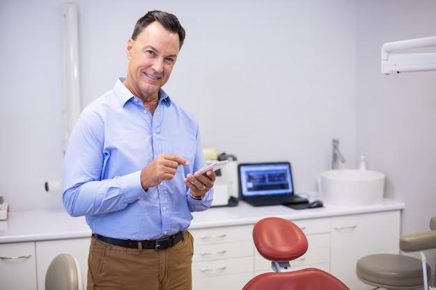 携帯電話を使用して笑顔の歯科医の肖像画