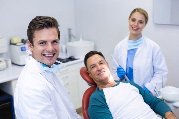 Портрет улыбающихся стоматологов и пациентов мужского пола