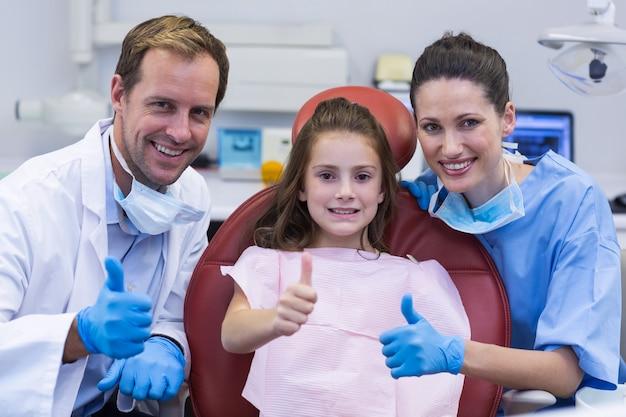 Портрет улыбающегося стоматолога и молодого пациента показывает палец вверх