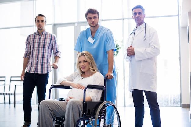 車椅子で妊娠中の女性を運ぶ笑顔の医者の肖像画