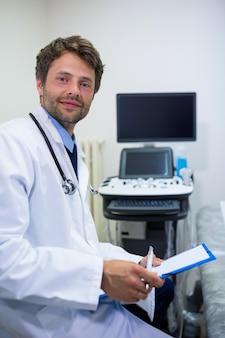 笑顔の医師保持クリップボードの肖像