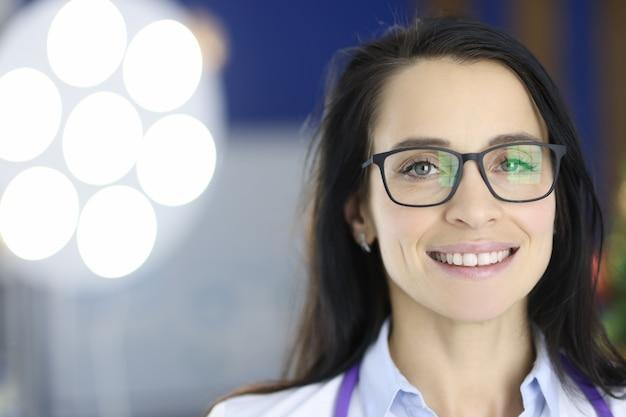 Портрет улыбающегося доктора в очках в операционной, спланированная концепция медицинских операций