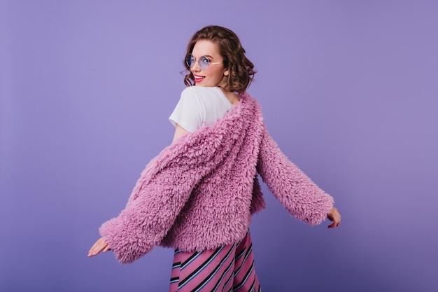 Портрет улыбающейся очаровательной девушки в меховой куртке, глядя через плечо. фотография в помещении эффектной кудрявой дамы, танцующей на фиолетовой стене в пушистом пальто.