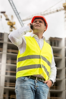 건물 사이트에 전화로 이야기하는 hardhat 및 안전 조끼에 웃는 엔지니어의 초상화