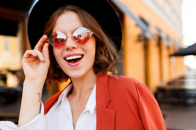 Портрет улыбающегося европейской девушки в милые оранжевые очки, куртка и черная шляпа. осенняя мода. уличное кафе.
