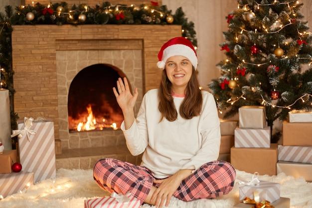 손을 흔들며 웃는 유럽 여자, 누군가 인사, 교차 다리와 함께 바닥에 앉아있는 동안 크리스마스 트리와 벽난로 배경에 포즈의 초상화.