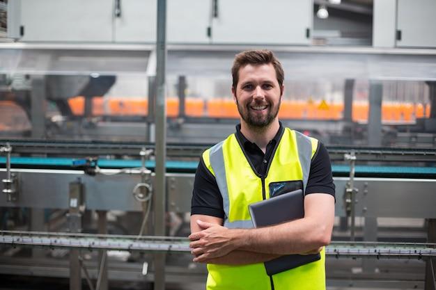 Портрет улыбающегося заводской рабочий, стоя с цифровой планшет