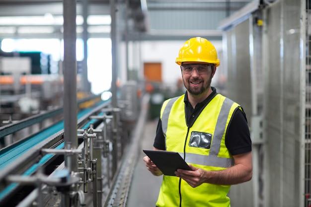 Портрет улыбающегося заводской рабочий с помощью цифрового планшета