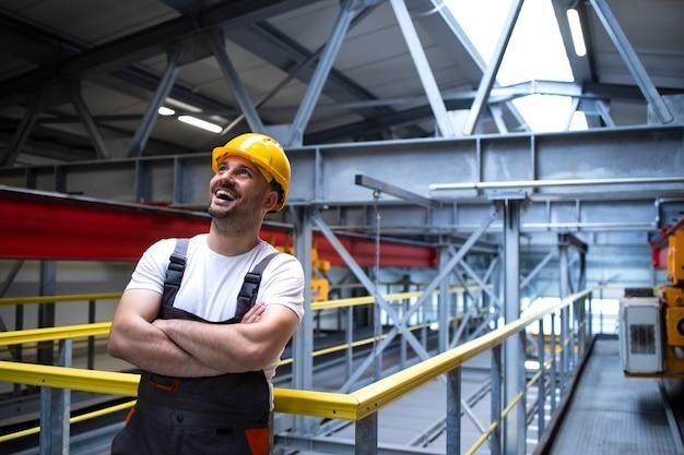 Портрет улыбающегося фабричного рабочего со скрещенными руками, стоящего в производственном цехе