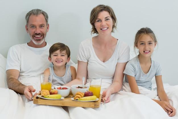 Портрет улыбающейся семьи, завтракающей на кровати в спальне