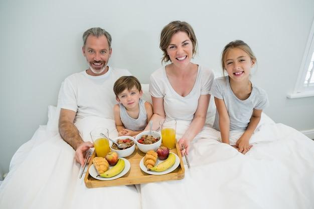 寝室のベッドで朝食を食べて笑顔の家族の肖像画
