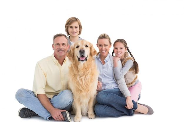 그들의 강아지와 함께 앉아 웃는 가족의 초상화