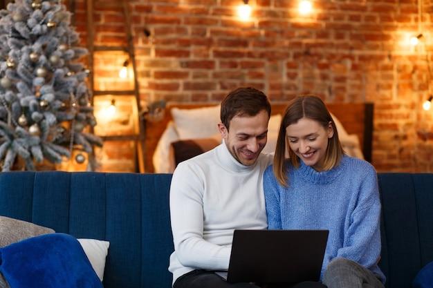 Портрет улыбающейся семьи, использующей ноутбук для онлайн-встречи, видеозвонка, видеоконференции с родителями, детьми, родственниками