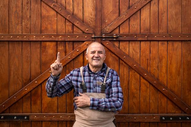 家畜農場で木造の納屋や穀倉のドアのそばに指を上に向けて立っている笑顔の農家の肖像画。