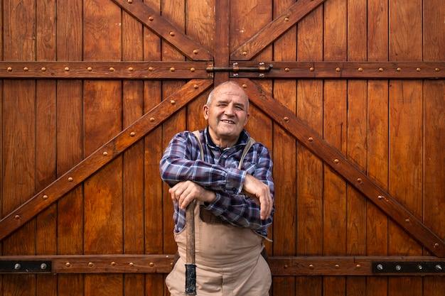 家畜農場で木造の納屋や穀倉のドアのそばに立っている笑顔の農家の肖像画。