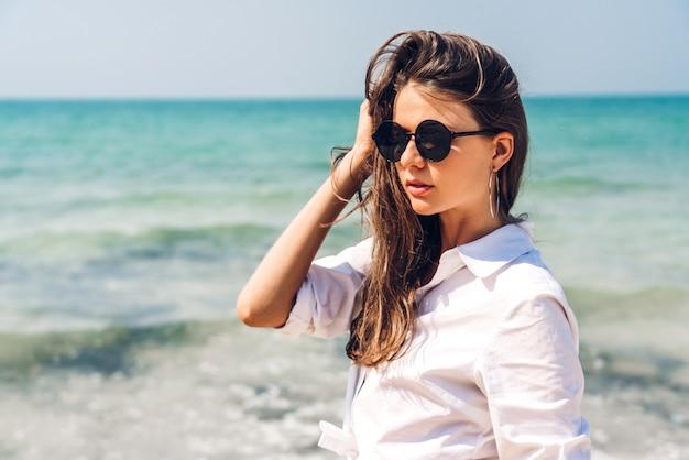 Портрет улыбающейся модной женщины релаксации на тропическом пляже. счастливая молодая красивая девушка, наслаждаясь и весело проводящая время на тропическом острове. летние каникулы